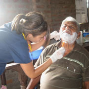 Nursing student shaving older man.